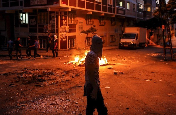 A far left-wing protester walks past a burning barricade during clashes with riot police in Istanbul's Gazi neighborhood