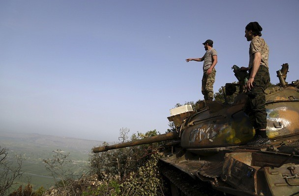 Rebel fighters stand on a tank overlooking al-Ghab plain, in the Jabal al-Akrad area in Syria's northwestern Latakia province