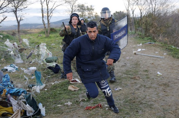 A migrant tries to escape from Macedonian police officers as he tries to cross the Greek-Macedonian border near the Greek village of Idomeni November 26, 2015. Countries along the Balkan route taken by hundreds of thousands of migrants seeking refuge in western Europe last week began filtering the flow, granting passage only to those fleeing conflict in Syria, Iraq and Afghanistan. REUTERS/Yannis Behrakis - RTX1VYUE